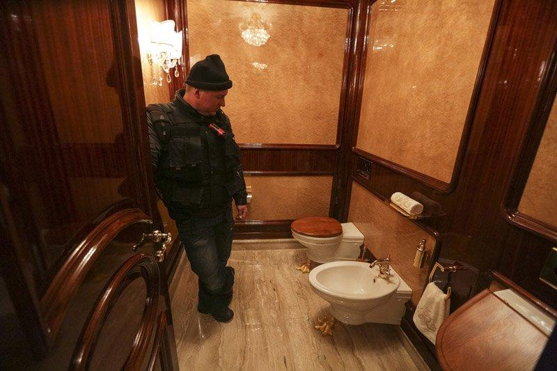 A man stands inside a lavatory as anti-government protesters and journalists walk on the grounds of the Mezhyhirya residence of Ukraine's President Yanukovich in Novi Petrivtsi