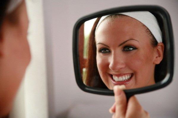 woman-looking-at-teeth-in-mirror