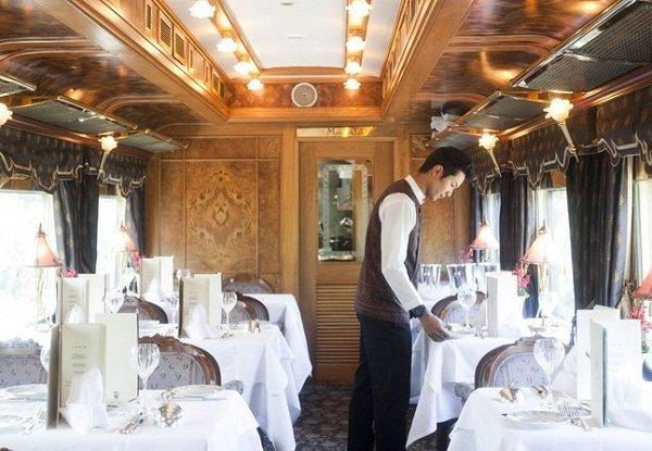 Waiters setting the table for lunch service on the Eastern & Oriental Express.
