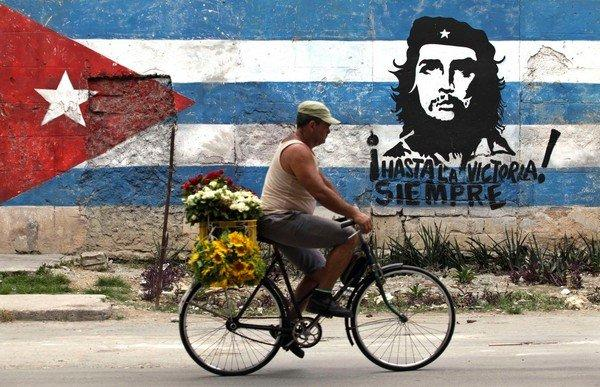 "A man rides his bicycle past a mural of rebel hero Ernesto ""Che"" Guevara and a Cuban flag in Havana"