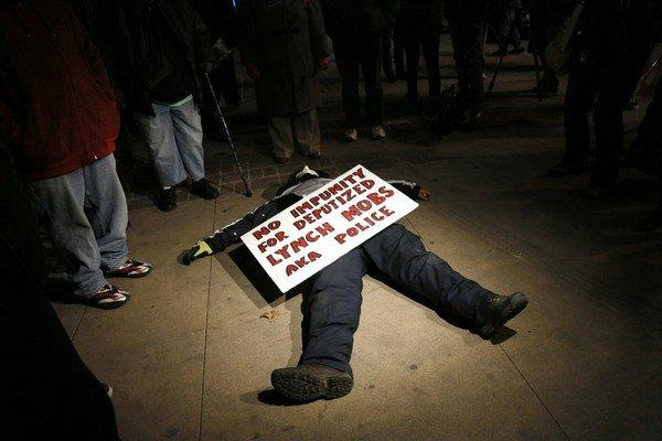 Protester lies on the sidewalk in downtown Denver