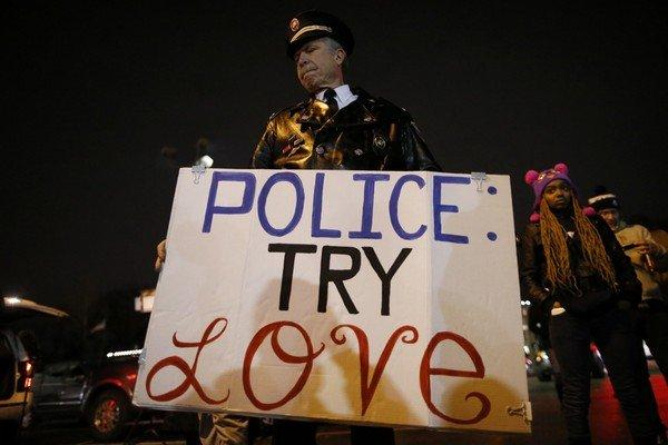 A man holds a sign outside the Ferguson Police Department in Ferguson