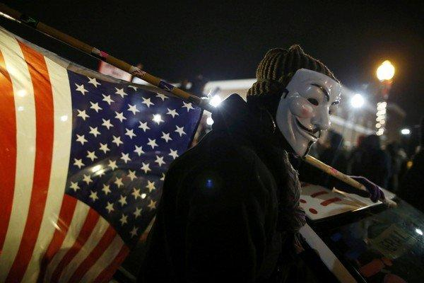 A protester wearing a Guy Fawkes mask carries an American flag outside the Ferguson Police Department in Ferguson, Missouri,