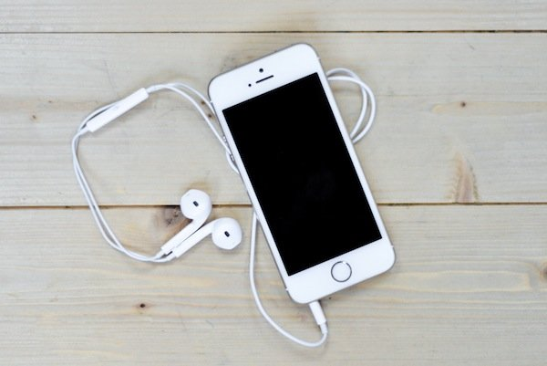 White-iPhone-On-Wooden-Desk-With-Headphones