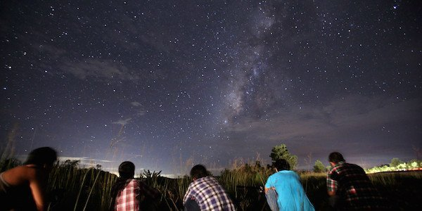 This long-exposure photograph taken on August 12, 2013 shows people watching for the Perseid meteor shower in the night sky near Yangon. The meteor shower occurs every year in August when the Earth passes through the debris and dust of the Swift-Tuttle comet.   AFP PHOTO / Ye Aung Thu        (Photo credit should read Ye Aung Thu/AFP/Getty Images)