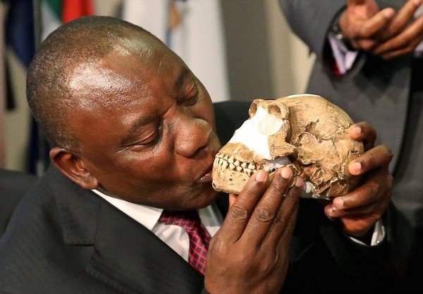 "South Africa's Deputy President Cyril Ramaphosa kisses a replica of the skull of a newly discovered ancient species, named ""Homo naledi"", during its unveiling outside Johannesburg"