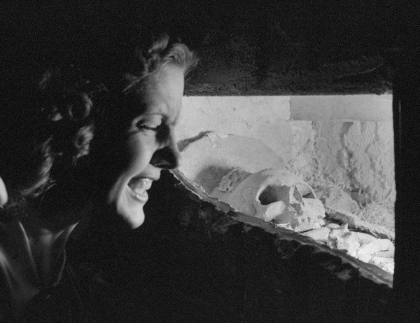 A woman looking at a plaster skull in th