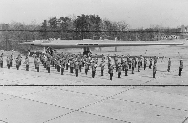 JUN 5 1949; With a giant B-49 flying wing in the background, the noted air force band prepares for i