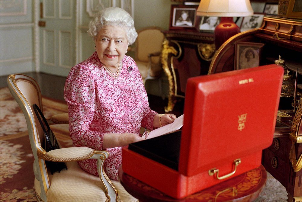Britain's Queen Elizabeth sits in her private audience room in Buckingham Palace next to one of her official red boxes in which she receives documents and papers from government officials in the United Kingdom and the Commonwealth in this handout photograph taken by Mary McCartney and released September 8, 2015 in London, to mark the moment she becomes Britain's longest reigning monarch. REUTERS/Mary McCartney/Copyright: Her Majesty Queen Elizabeth II/Handout via Reuters ATTENTION EDITORS - THIS IMAGE HAS BEEN SUPPLIED BY A THIRD PARTY. IT IS DISTRIBUTED, EXACTLY AS RECEIVED BY REUTERS, AS A SERVICE TO CLIENTS. FOR EDITORIAL USE ONLY. NOT FOR SALE FOR MARKETING OR ADVERTISING CAMPAIGNS. NO SALES. This image is free of charge for a month from release. Use or reproduction in any format on any platform after October 8, 2015, must be approved first by Royal Communications at Buckingham Palace. TPX IMAGES OF THE DAY