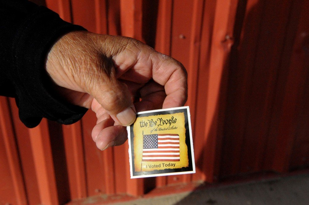 A person displays a card received after voting at a polling station on the Standing Rock Indian Reservation in Cannon Ball, North Dakota