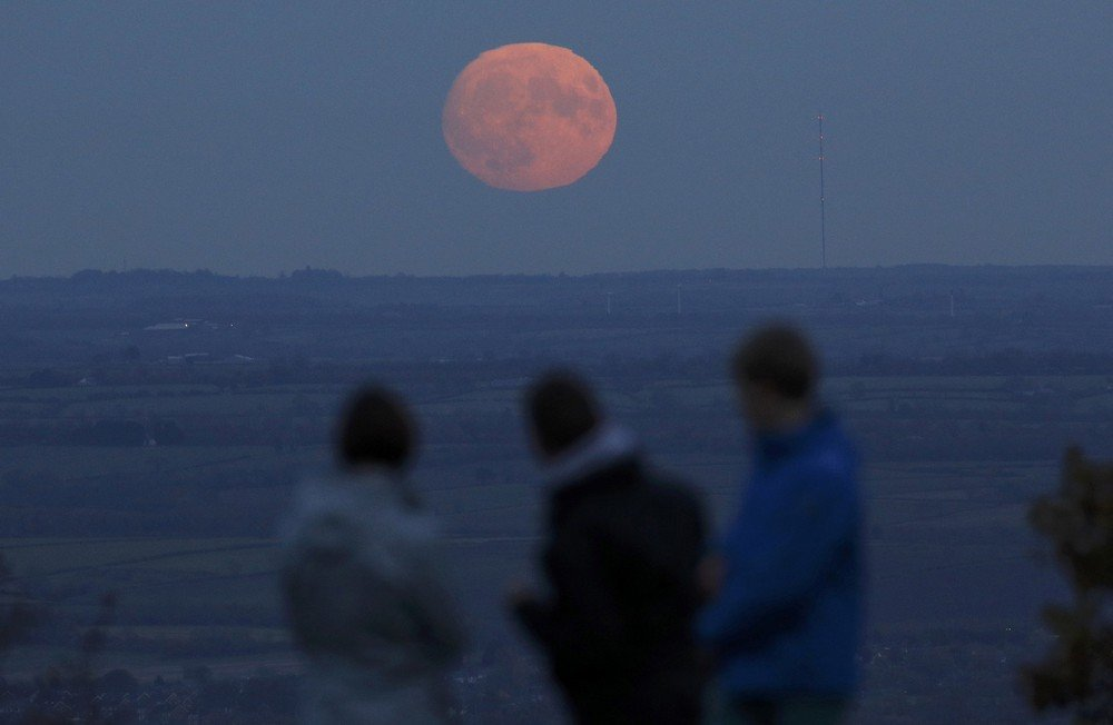 "A family watch the moon rise a day before the ""supermoon"" spectacle on Beacon Hill near Loughborough"