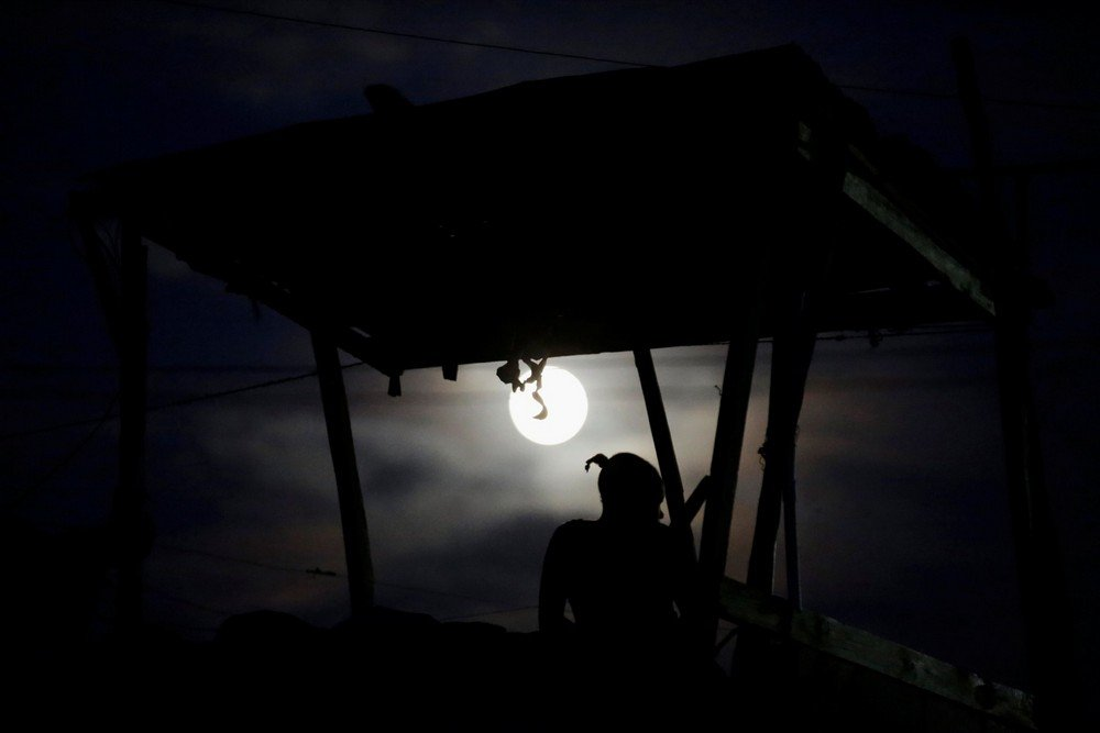 "A woman sits on the rooftop terrace of a house during the ""supermoon"" in Port-au-Prince, Haiti"