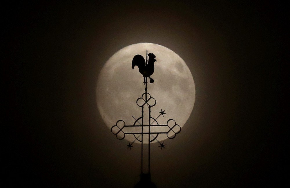 "The weathercock of the church of St.Peter and Paul is seen in front of a moon on the eve of the ""supermoon"" spectacle in the village of Klein-Auheim near Hanau"