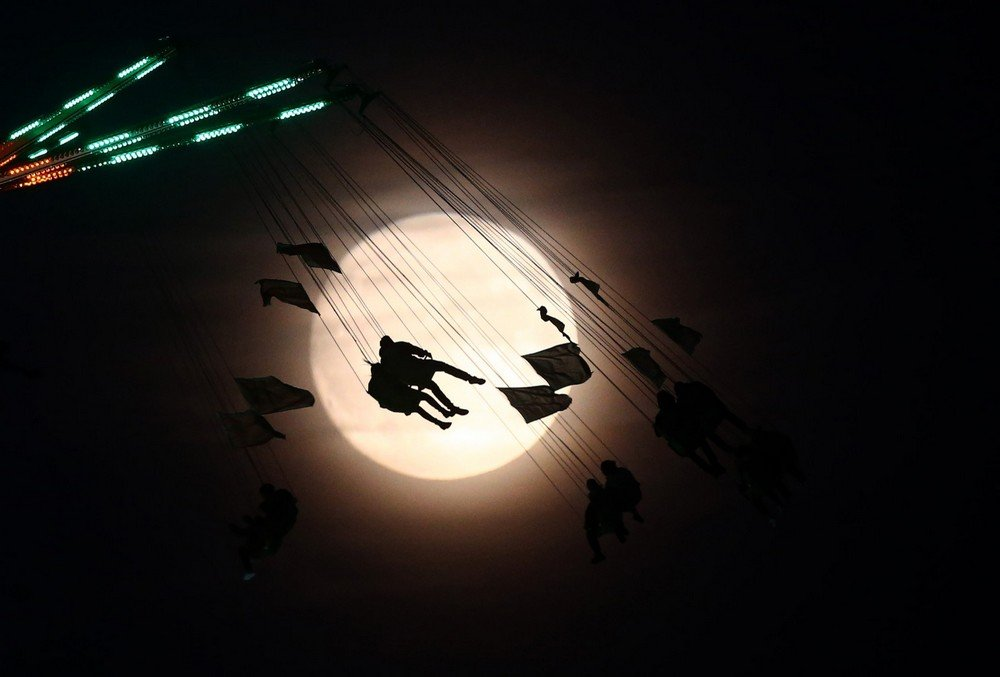 """People on a funfair ride are silhouetted against the moon a day before the """"supermoon"""" spectacle, in London"""