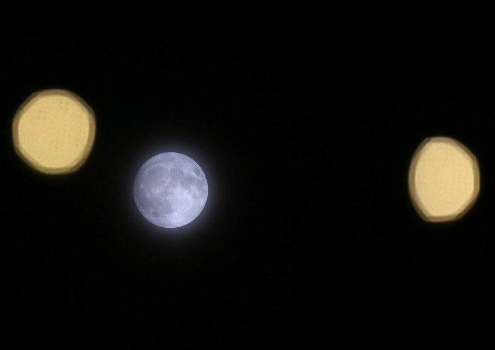 "Streetlights are seen next to the moon a day before the ""supermoon"" spectacle, in London"